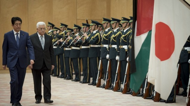 رئيس السلطة الفلسطينية محمود عباس (الثاني من اليسار) يسير إلى جانب رئيس الوزراء الياباني شينزو ابي (من اليسار) أما حرس الشرف قبيل إجتماعهما في مقر إقامة ابي الرسمي في طوكيو، 15 فبراير، 2016. (Nicolas Datiche/AFP)