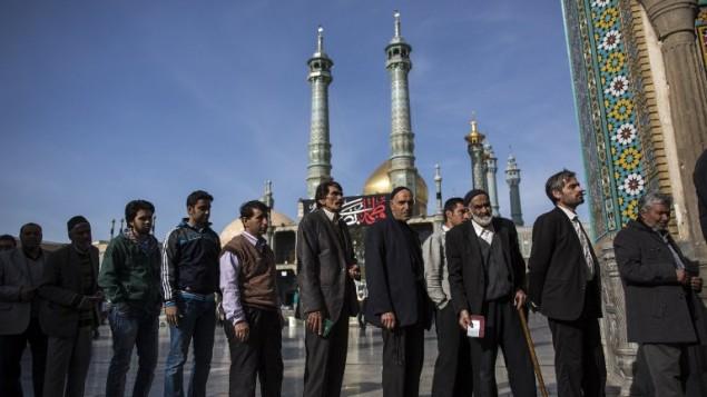 رجال إيرانيون ينتظرون للادلاء بصوتهم في مدينة قم، 26 فبراير 2016 (BEHROUZ MEHRI / AFP)