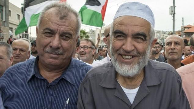 رئيس الحركة الإسلامية، الشخي رائد صلاح (من اليمين) وعضو الكنيست السابق، محمد بركة، خلال تظاهرة في مدينة سخنين في 13 أكتوبر، 2015. (AFP PHOTO/JACK GUEZ)
