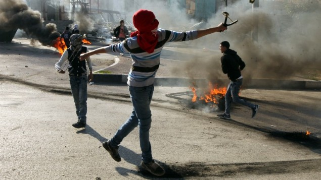 مراهقين فلسطينيين يرشقون قوات الامن الإسرائيلية بالحجارة خلال اشتباكات في مدينة الخليل في الضفة الغربية، 20 نوفمبر 2015 (AFP/Hazem Bader)