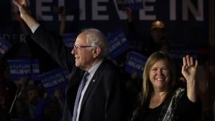 المرشح الديمقراطي للرئاسة برني ساندرز (مستقل-فيرمونت) وزوجته جين أوميرا  سنادرز على المنصة خلال ليلة الإنتخابات التمهيدية للحزب الديمقراطي في 1 فبراير، 2016 في دي موين بولاية أيوا (Alex Wong/Getty Images/AFP)