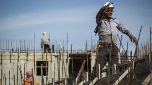 عمال فلسطينيون يعملون على بناء وحدات سكنية جديدة في حي هار حوما في القدس الشرقية، 28 أكتوبر، 2014. (Hadas Parush/Flash90)