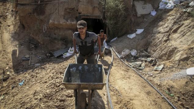 رجال فلسطينيون يعملون عند مدخل نفق يستخدم لتهريب البضائع بين مصر وقطاع غزة، بعد إغراقه بمياه البحر على يد الجيش المصري، في رفح جنوبي غزة، 1 أكتوبر، 2015. (Abed Rahim Khatib/ Flash90)