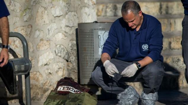 محقق شرطة بالقرب من جثث منفذي هجوم فلسطينيين في موقع هجوم إطلاق النار والطعن بالقرب من باب العامود في القدس، 3 فبراير، 2016. (Yonatan Sindel/Flash90)
