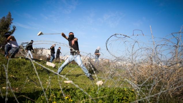صورة توضيحية: فلسطيني يستخد المقلاع لإلقاء الحجارة بإتجاه القوات الإسرائيلية (الغير ظاهرة بالصورة) خلال مواجهات بالقرب من مدينة رام الله في الضفة الغربية، 12 فبراير، 2016. (Flash90)