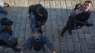 عناصر شرطة يفتشون رجل فلسطيني في باب العامود في القدس، 15 فبراير 2016 (Nati Shohat/Flash90)