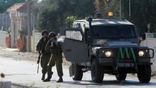 جندي اسرائيلي يطلق قنبلة غاز اثناء مظاهرة في بلدة سلواد في الضفة الغربية، 15 اغسطس 2014 (AFP/ Abbas Momani)