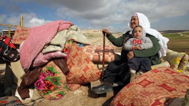 سيدة فلسطينية تجلس وهي تحمل طفبلا إلى جانب ما تم إنقاذه من بقايا منزلهما بعد أن قامت الجرافات الإسرائيلية بهدمه في منطقة عسكرية متنازع عليها في مسافر جنبا، التي تضم عددا من القرى، جنوبي مدينة الخليل في الضفة الغربية، 2 فبراير، 2016.  (AFP / HAZEM BADER)