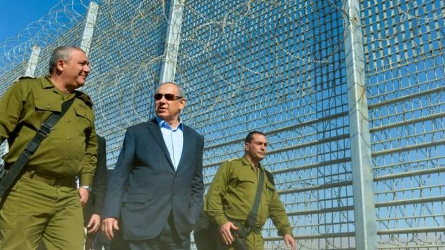 رئيس الوزراء بينيامين نتنياهو ورئيسة هيئة الأركان العامة للجيش الإسرائيلي غادي آيزنكوت خلال زيارة لأعمال بناء على السياج الحدودي بين إسرائيل والأردن، 9 فبراير، 2016. (Kobi Gideon/GPO)