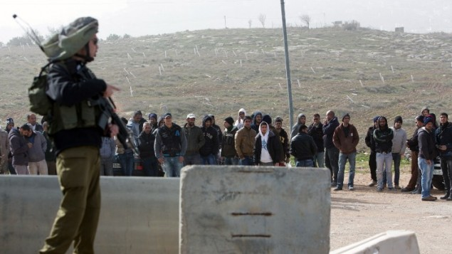 جندي إسرائيلي يقف بالقرب من عمال فلسطينيين تم إخراجهم من مستوطنة تقوع جنوبي القدس في أعقاب هجوم وقع فيها في 18 يناير، 2016. (AFP / MENAHEM KAHANA)