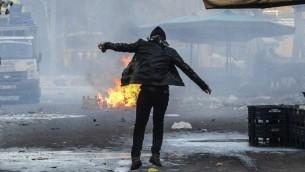 رجل يقف امام نيران مشتعلة في الشارع خلال اشتباكات بين اكراد وقوات تركية في مركز مدينة ديار بكر، 2 مارس 2016 (ILYAS AKENGIN / AFP)