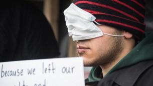 مهاجر إيراني في مخيم كاليه الفرنسي للاجئين، خيط شفاه احتجاجا على هدم خيمته في المخيم، 3 مارس 2016 (DENIS CHARLET / AFP)