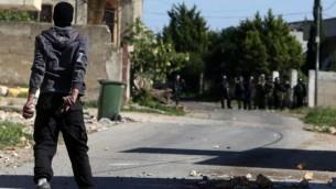 محتج فلسطيني في مواجهة القوات الإسرائيلية خلال اشتباكات في قرية كفر قدوم قرب نابلس، في الضفة الغربية، 11 مارس، 2016. (AFP/Jaafar Ashtiyeh)