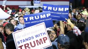 متظاهر محاط بداعمي دونالد ترامب بينما يحاول مقاطعة المرشح الجمهوري في فلوريدا، 13 مارس 2016 (RHONA WISE / AFP)