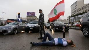 متظاهرة لبنانية تستلقى في شارع سريع بشكل احد المداخل الرئيسية للعاصمة بيروت وتحمل علم لبنان احتجاجا على قرار السلطات اعادة فتح المطامر للتعامل مع ازمة النفايات المتراكمة، 14 مارس 2016 (MARWAN TAHTAH / AFP)