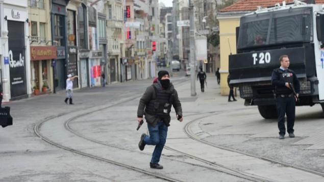 رجل شرطة تركي يركض في شارع إستقلال بمدينة إسطنبول في 19 مارس، 2016، بعد مقتل 4 أشخاص وغصابة 36 آخرين في هجوم إنتحاري. (Bulent Kilic/AFP)