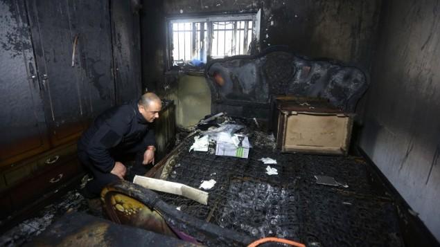 شرطي فلسطيني يتفحص الاضرار في منزل ابراهيم دوابشة، الشاهد المركزي في قضية هجوم الصيف الماضي في دوما، حيث قتل ثلاثة من افراد عائلة دوابشة، 20 مارس 2016 (AFP/Jaafar Ashtiyeh)