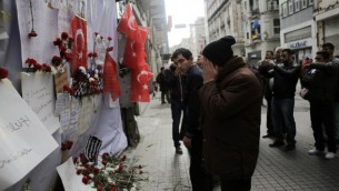 رجل يقف أمام نصب تذكاري مؤقت في موقع التفجير الإنتحاري في شارع إستقلال السياحي وسط إسطنبول، 20 مارس، 2016. (AFP / YASIN AKGUL)