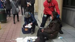 حارس أمني خاص يساعد امرأة مصابة امام محطة المترو مالبيك في بروكسل، 22 مارس 2016 (AFP/Michael VILLA)