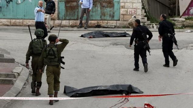 جنود إسرائيليون والشرطة يحيطون بجثتي منفذي هجوم فلسطينيين قُتلا بعد أن هاجما جندي إسرائيلي بسكين مما أدى إلى إصابته قبل أن يُقتلا بنيران الوقوات الإسرائيلية، بحسب متحدث بإسم الجيش، عند مدخل حي تل الرميدة في مدينة الخليل بالضفة الغربية، 24 مارس، 2016. (AFP / HAZEM BADER)