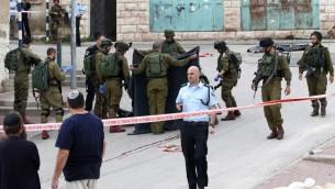 جنود اسرائيليون يغطون جثمان المعتدي الفلسطيني الذي قُتل برصاص جندي اطلق النار على رأسه بينما كان ملقى مصاب على الارض بعد طعنه جندي في الخليل، 24 مارس 2016 (AFP / HAZEM BADER)