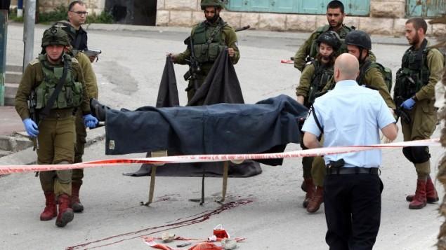 جنود إسرائيليون يحملون جثة أحد الفلسطينيين اللذين قُتلا بعد مهاجمتهما لجندي إسرائيلي في هجوم طعن قبل أن يُقتلا بنيران القوات الإسرائيلية عند مدخل حي تل الرميدة اليهودي وسط مدينة الخليل ف الضفة الغربية، 24 مارس، 2016. (AFP/Hazem Bader)