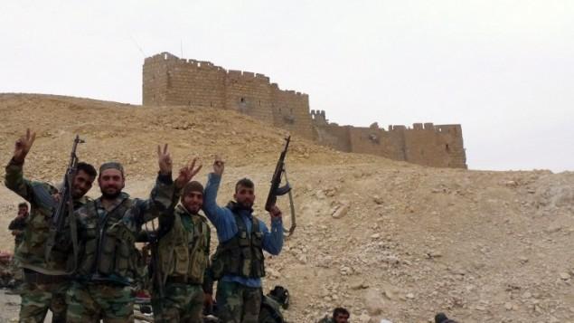 قوات موالية للنظام السوري تقف بجانب قلعة تدمر في 26 مارس، 2016، خلال عملية عسكرية لإعادة الإستيلاء على البلدة الأثرية من تنظيم 'الدولة الإسلامية'. (AFP / Maher AL MOUNES)