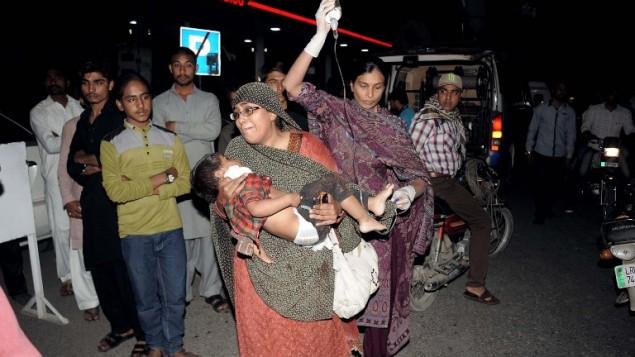 أقارب باكستانيون يحضرون طفلا مصابا إلى المستشفى في لاهور في 27 مارس، 2016، بعد مقتل 72 شخص على الأقل وإصابة 340 عندما قام انتحاري بتفجير نفسه في موقف سيارات لمتنزه مكتظ في مدينة لاهور الباكستانية حيث احتفل المسيحيون بعيد الفصح. (AFP/ARIF ALI)