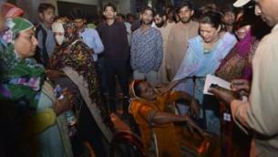 أقارب باكستانيون يحضرون مصابين  إلى المستشفى في لاهور في 27 مارس، 2016، بعد مقتل 72 شخص على الأقل وإصابة 340 عندما قام انتحاري بتفجير نفسه في موقف سيارات لمتنزه مكتظ في مدينة لاهور الباكستانية حيث احتفل المسيحيون بعيد الفصح. (AFP/ARIF ALI)