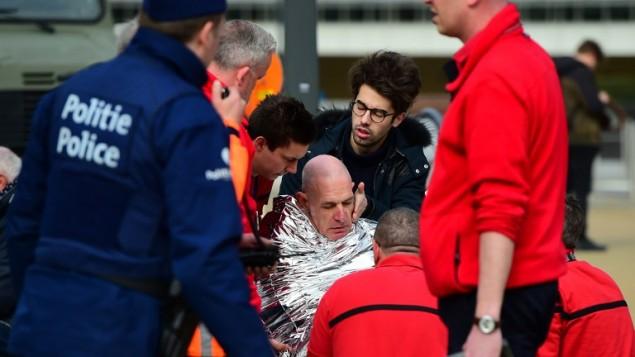 أحد الضحايا يتلقى الإسعاف الأولي في 22 مارس، 2016 بالقرب من محطة المترو مالبيك في بروكسل، بعد أن هز انفجار المحطة القريبة من مؤسسات الإتحاد الأوروبي وأسفر وقوع قتلى وجرحى. (AFP PHOTO / EMMANUEL DUNAND / AFP / EMMANUEL DUNAND)