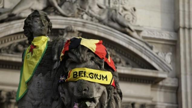 العلم البلجيكي يلف تمثالا في نصب تذكاري مرتجل عند 'بلاس دو لا بورس' في بروكسل في 23 مارس، 2016، بعد يوم من التفجيرات التي هزت العاصمة البلجيكية. (AFP PHOTO/KENZO TRIBOUILLARD)
