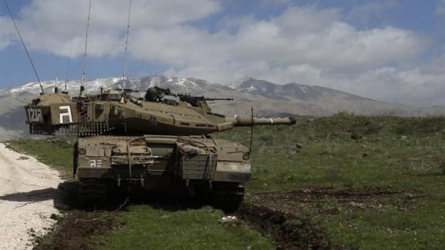 صورة أرشيفية: دبابة تابعة للجيش الإسرائيلي متمركزة بالقرب من قرية مجدل شمس، 19 مارس، 2014، في هضبة الجولان. (AFP/Jalaa Marey)