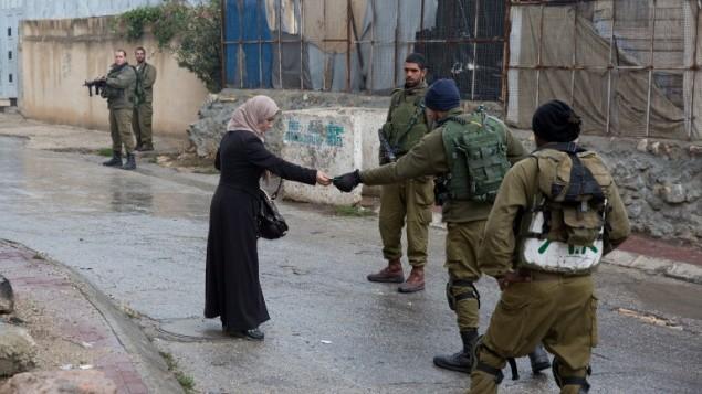 صورة توضيحية: جنود إسرائيليون يتحققون من هوية سيدة فلسطينية بالقرب من مستوطنة يهودية في الخليل، 29 أكتوبر، 2015. (AFP/Menahem Kahana)