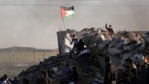 من الأرشيف: متظاهر فلسطيني يرفع العلم الفلسطيني خلال مواجهات مع القوات الإسرائيلية على الحدود مع إسرائيل في الضواحي الجنوبية لمدينة غزة في 4 ديسمبر، 2015. (AFP PHOTO/MAHMUD HAMS)