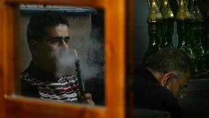 صورة توضيحية لرجل يدخن النرجيلة في مقهى (Michal Fattal/Flash90)