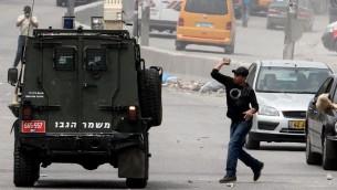 متظاهرون فلسطينيون يرشقون مركبة عسكرية اسرائيلية بالحجارة خلال مظاهرة عند مدخل حاجز قلنديا، 30 مارس 2013 (Issam Rimawi/Flash90)