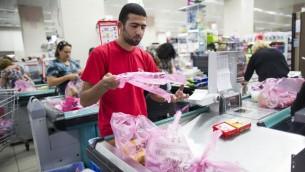 عامل في متجر ,رامي ليفي' في سوق تلبيوت في القدس يغلف متوجات بالاكياس البلاستيكية، 3 سبتمبر 2013 (Yonatan Sindel/Flash90)