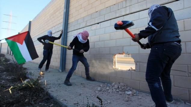 فلسطينيون يقومون بتحطيم مقطع من الجدار الفاصل في الضفة الغربية في قرية بير نبالا، بين القدس ورام الله، 8 نوفمبر، 2014. (STR/Flash90)