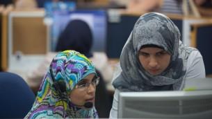 """نساء بدويات يعملن في مركز خدمة العملاء التابع لشركة """"بيزك"""" في 27 يوليو، 2015. مركز الخدمات الهاتفية يقع في مسجد، في بلدة الحورة العربية.  تم تشغيل النساء من خلال مركز """"ريان"""" للتشغيل في مدينة رهط. خبراء التوظيف يقولون بأنهم يريدون التركيز على مسارات مهنية ذات جودة بالإضافة إلى وظائف على مستوى مبتدئين. (Miriam Alster/Flash90)"""
