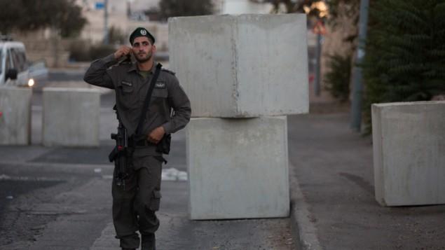 عنصر من شرطة حرس الحدود يقف عند حاجز طريق تم وضعه عند مدخل حي جبل المكبر في القدس الشرقية، 14 أكتوبر، 2015. (Yonatan Sindel/Flash90)