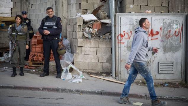 صورة توضيحية لرجل فلسطيني يمر امام عناصر امن اسرائيليين عند مدخل مخيم شعفاط في القدس الشرقية، 2 ديسمبر 2015 (Hadas Parush/Flash90)