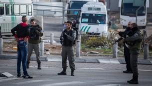 صورة توضيحية لقوات الامن الإسرائيلية توقف شاب فلسطيني عند مدخل مخيم شعفاط في القدس الشرقية، 2 ديسمبر 2015 (Hadas Parush/Flash90)