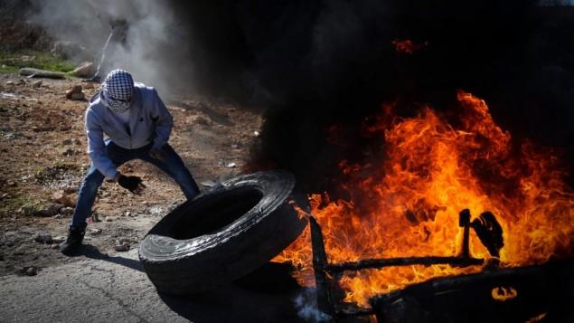 متظاهر فلسطيني يشعل إطار سيارة خلال مواجهات في الضفة الغربية، 5 ديسمبر 2015 (FLASH90)