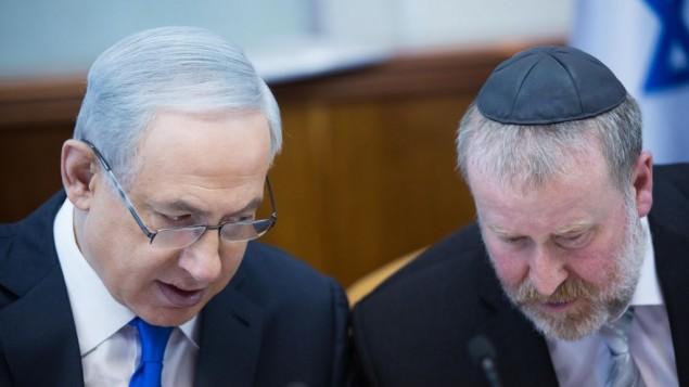رئيس الوزراء بينيامين نتنياهو (من اليسار) يتحدث مع أفيحاي ماندلبليت، سكرتير الحكومة في ذلك الوقت، خلال الجلسة الأسبوعية للمجلس الوزاري في القدس، 20 ديسمبر، 2015. (Yonatan Sindel/Flash90)