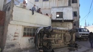 فلسطينيون ينظرون الى الدمار الناتج عن اشتباكات بين السكان وقوات الامن الإسرائيلية في مخيم قلنديا، 1 مارس 2016 (Flash90)