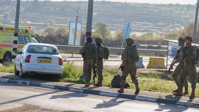 قوات امن اسرائيلية تقترب من سيارة معتدي فلسطيني في مفترق عتصيون، 4 مارس 2016 (Gershon Elinson/Flash90)