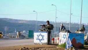 قوات أمن إسرائيلية بالقرب من موقع هجوم الدهس الذي وقع بالقرب من مفرق غوش عتصيون في الضفة الغربية، 4 مارس، 2016. (Gershon Elinson/Flash90)