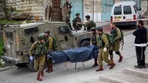 جنود إسرائيليون ينقلون جثة شاب فلسطيني قُتل جراء إطلاق النار عليه بعد أن قام بطعن جندي في مدينة الخليل بالضفة الغربية، 24 مارس، 2016. (Wissam Hashlamon/Flash90)