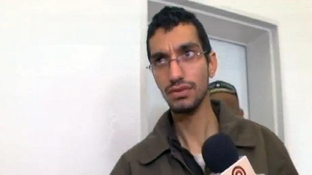 مجد عويضة، 22 عاما، من سكان قطاع غزة والذي تتهمه إسرائيل بإختراق أنظمة طائرات بدون طيار تابعة للجيش الإسرائيلي وكاميرات مرور وأنظمة كمبيوتر، في محكمة في مدينة بئر السبع في 23 مارس، 2016. (لقطة شاشة: القناة 10)