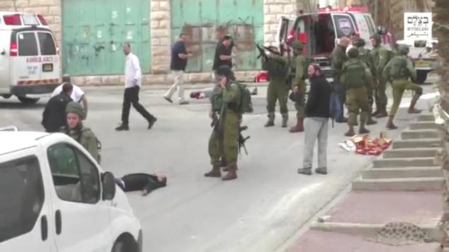 جندي إسرائيلي يقوم بتمشيط سلاحه قبل أن يقوم بإطلاق النار كما يبدو على منفذ هجوم فلسطيني منزوع السلاح وملقى على الأرض في رأسه في أعقاب هجوم طعن في الخليل، 24 مارس، 2016. (لقطة شاشة: بتسيلم)